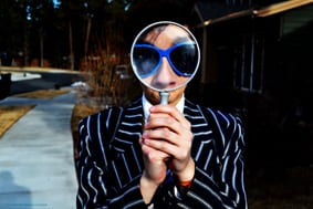 Man looking through magnifying glass at the camera wearing a striped blazer and sunglasses