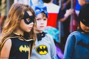 Three children wearing superhero costumes