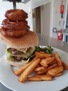 Double hamburger with onion rings and chips on a plate
